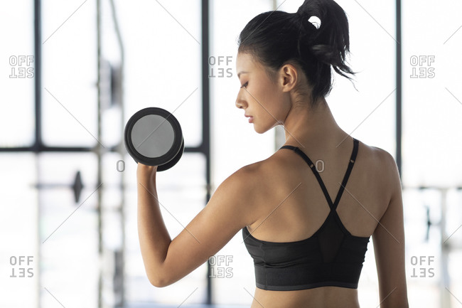 Young Chinese woman exercising with dumbbell at gym