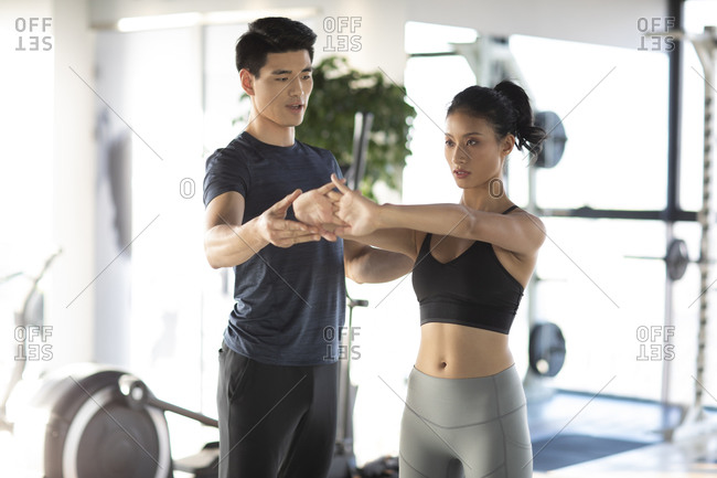 Young Chinese woman working out with personal trainer at gym