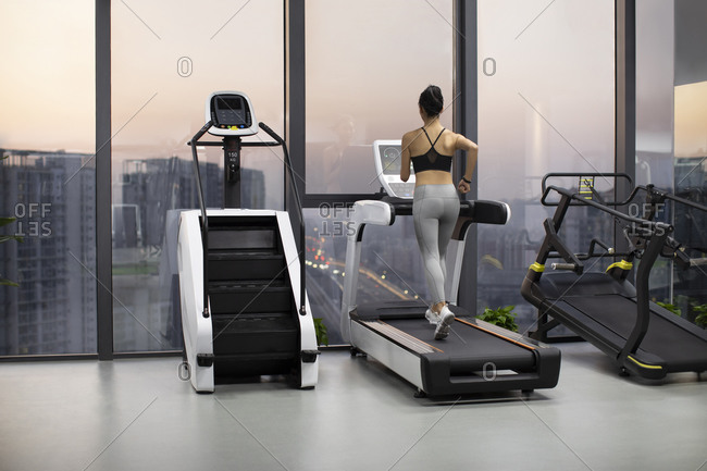 Young Chinese woman exercising on treadmill at gym