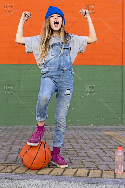 Young girl with foot on basketball
