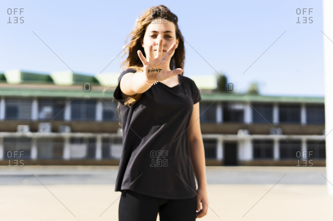 Portrait of serious teenage girl showing the word fight written on her palm