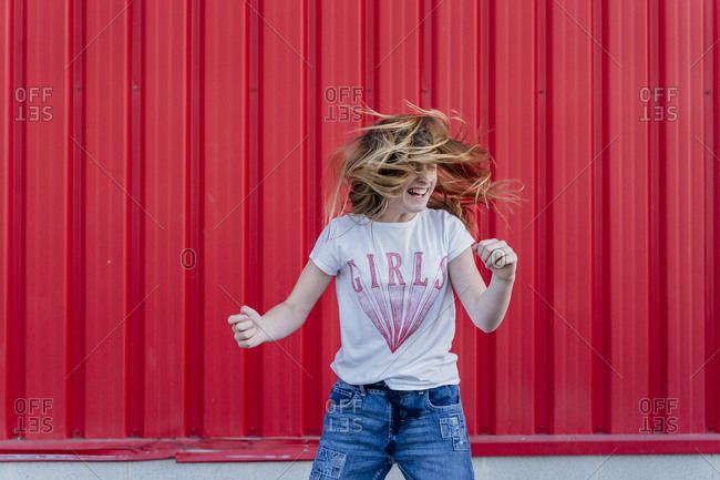 Girl headbanging in front of red wall