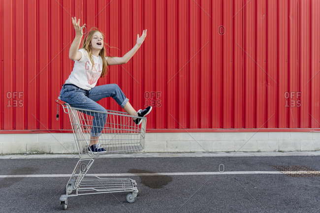 Girl in a shopping cart in front of red wall