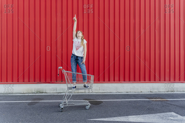 Girl in a shopping cart pointing finger up in front of red wall