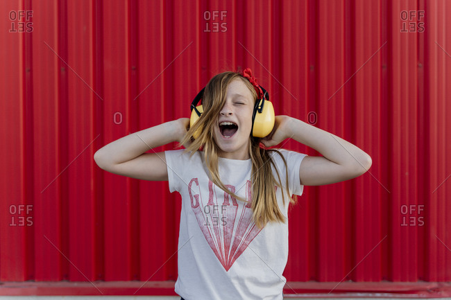 Girl with ear defenders in front of red wall