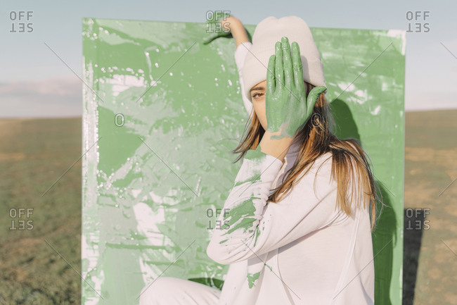 Young woman standing in front of painting- covering eye with green hand