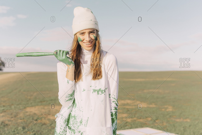 Young woman with green paint on her hands- holding stick- laughing