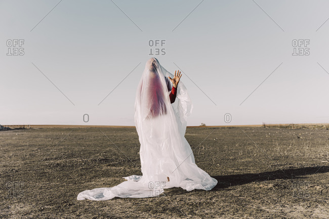 Young man standing in barren land trapped in a plastic foil