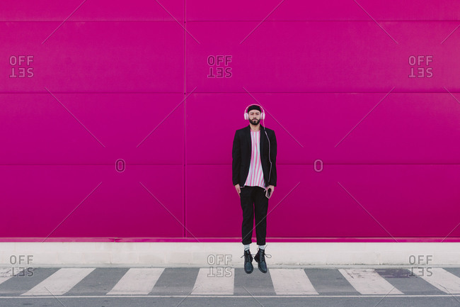 Businessman walking along a pink wall