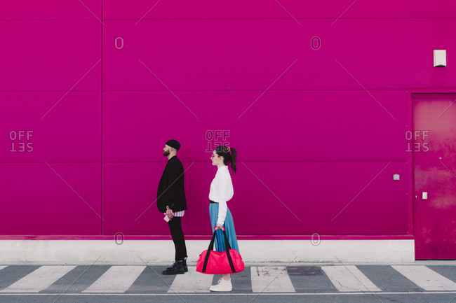 Man and woman standing on a pink wall- looking away