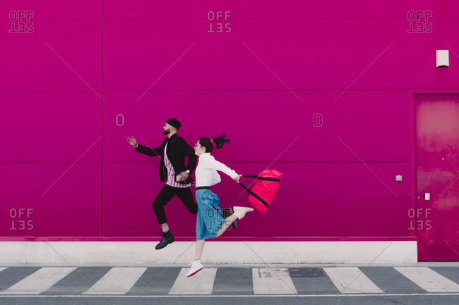 Man and woman running along a pink wall
