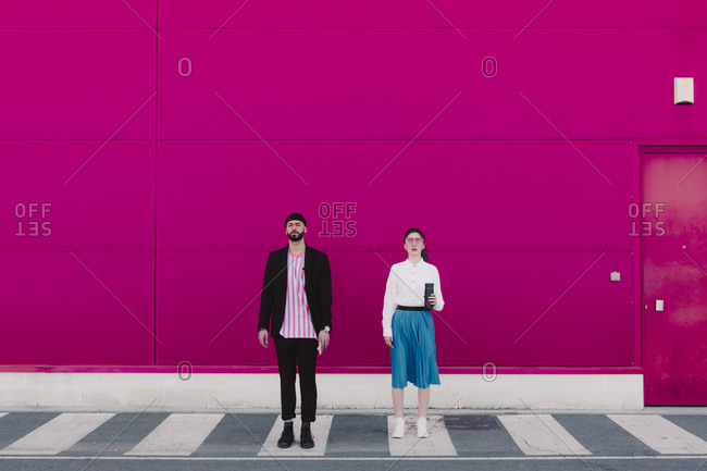 Man with smartphone and woman with coffee to go standing on white stripes