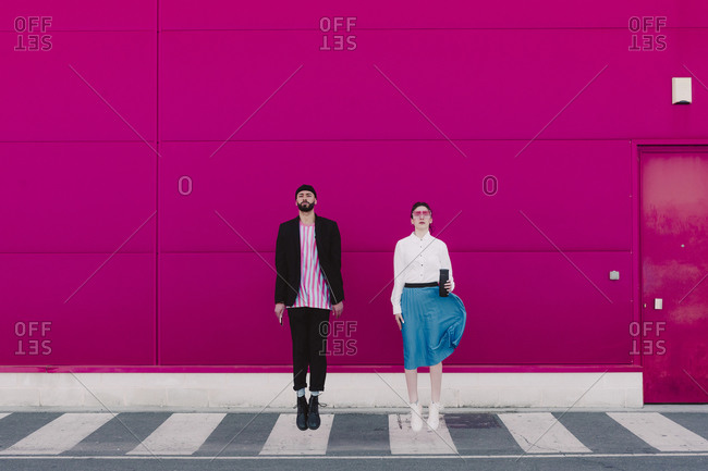Man with smartphone and woman with coffee to go jumping in front of a pink wall