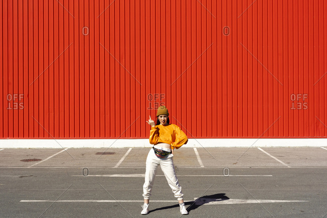 Young woman posing in front of a red wall