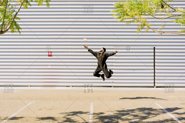Man wearing black overall jumping in the air in front of industrial building