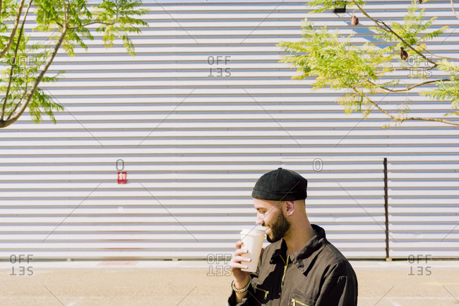 Smiling man with coffee to go in front of industrial building