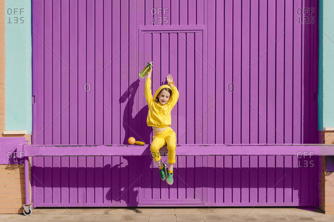 Happy little girl dressed in yellow sitting on bar in front of purple garage door