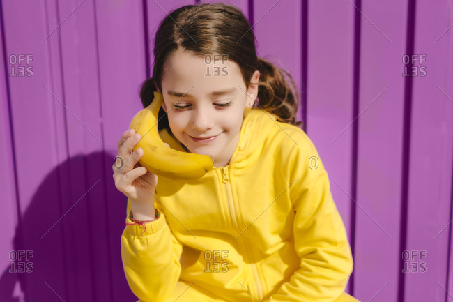 Portrait of smiling girl dressed in yellow holding banana in front of purple background