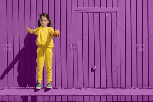 Portrait of little girl dressed in yellow standing in front of purple background offering fruits