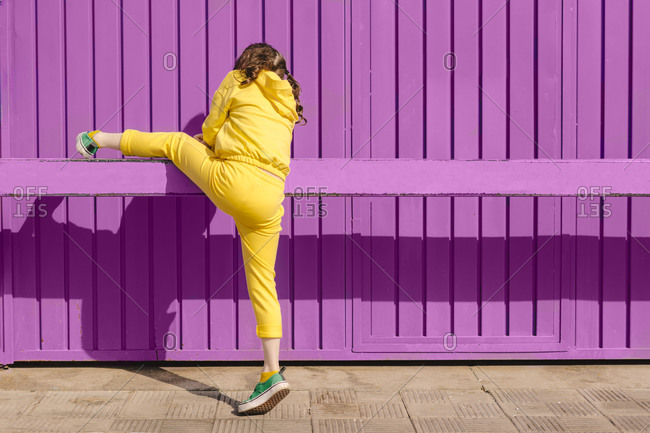 Back view of girl dressed in yellow climbing on bar in front of purple background