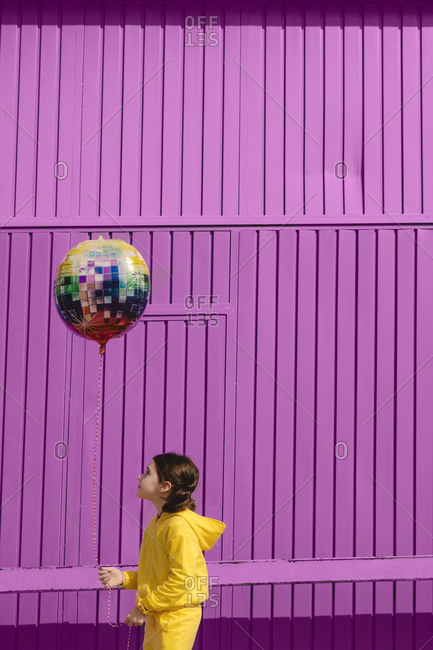 Little girl dressed in yellow holding balloon in front of purple background