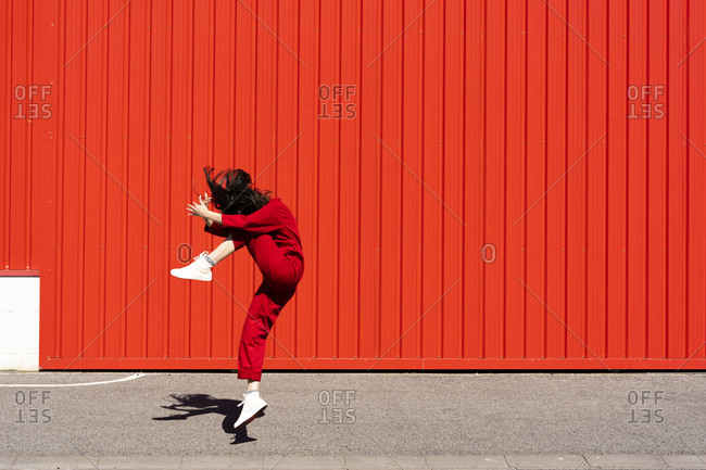 Woman dressed in red overall jumping in the air in front of red roller shutter