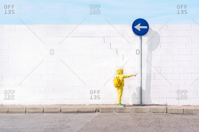 Girl with her toy on a traffic sign- direction left in front of a white wall