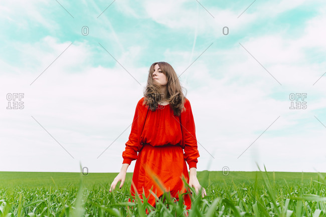 Woman wearing red dress relaxing in a field with eyes closed