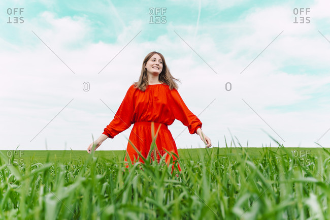 Smiling woman wearing red dress standing in a field
