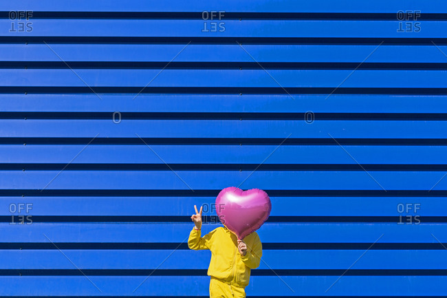 Little girl standing in front of blue background hiding behind pink balloon and showing victory sign