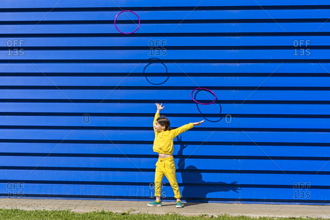 Little girl wearing yellow tracksuit throwing gymnastic rings in the air in front of blue background