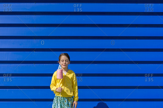 Little girl with fake ice cream standing in front of blue background licking lips