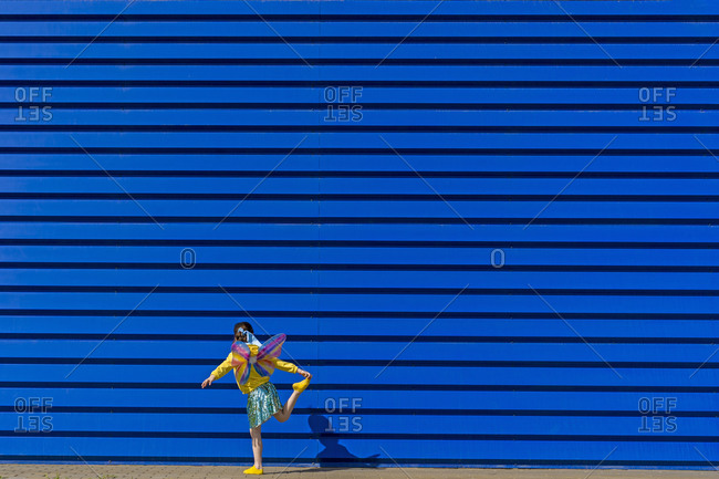 Back view of little girl with colorful butterfly wings balancing on one leg in front of blue background