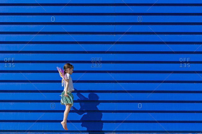Little girl with colorful butterfly wings jumping in the air in front of blue background