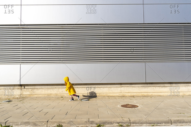 Little girl wearing yellow rain coat running on pavement