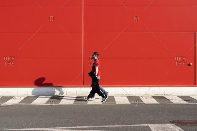 Man walking with his little girl wearing black fancy dress on zebra crossing