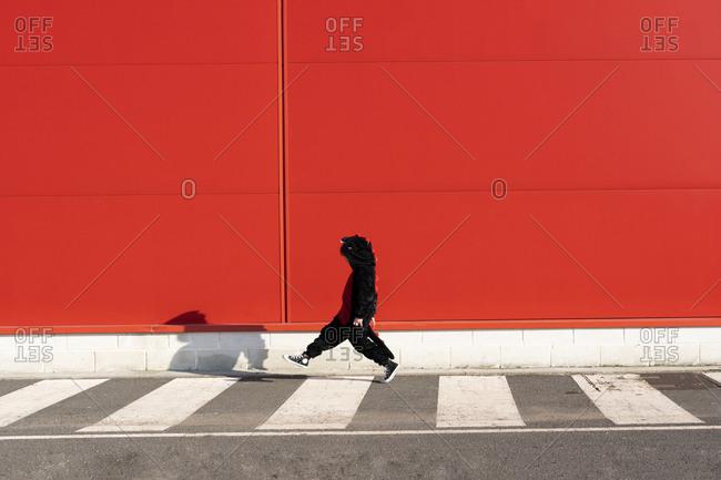 Little girl wearing black fancy dress walking on zebra crossing