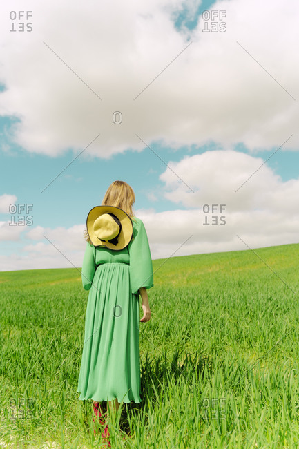 Back view of woman wearing green dress standing on a field