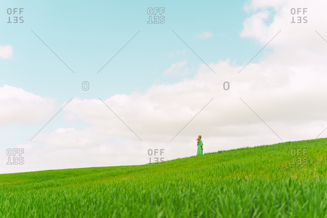 Back view of woman wearing green dress standing on a field looking at distance