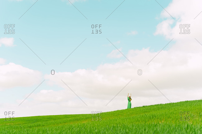 Back view of woman wearing green dress standing on a field with hands raised