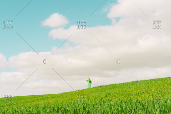 Back view of woman wearing green dress and summer hat standing on a field looking at distance