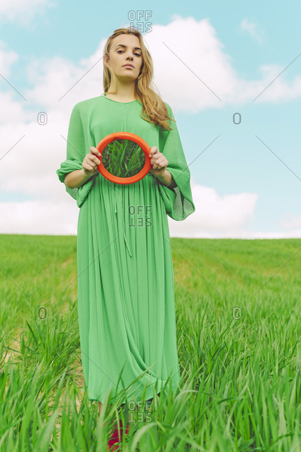 Portrait of young woman wearing green dress standing on a field holding reflecting mirror