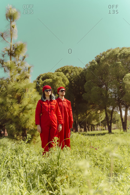 Young couple wearing red overalls and hats standing on a meadow looking at distance