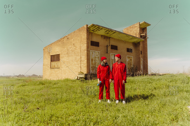 Young couple wearing red overalls and hats standing on a meadow in front of industrial building
