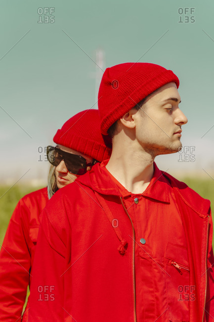 Young couple with eyes closed dressed in red outdoors