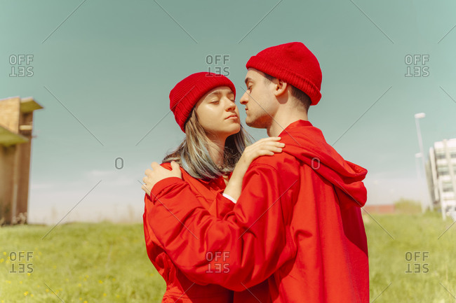 Young couple wearing red overalls and hats standing on a meadow