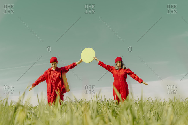 Young couple wearing red overalls and hats standing on a field holding green circle