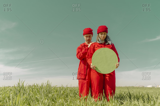 Young couple wearing red overalls and hats standing on a field with green circle