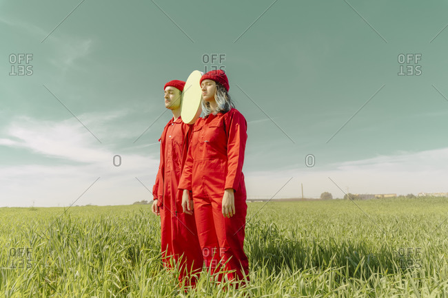 Young couple wearing red overalls  standing on a field with green circle