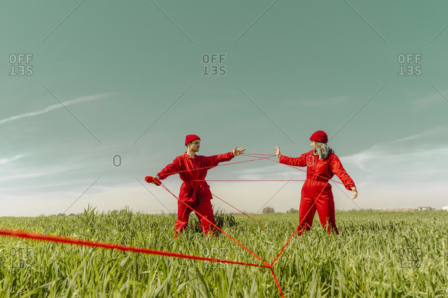 Young couple wearing red overalls and hats performing on a field with red string